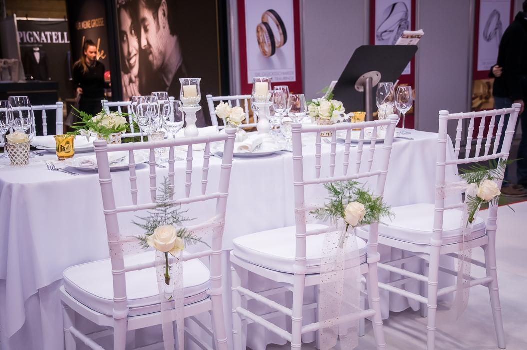 Tischdekoration auf der Trau Hochzeitsmesse. Weisse Stühle mit weissen Tellern und gelben schönen Blumen mit Schleifen. Eine sehr schöne Hochzeitdekoratinen. Festliche Stimmung