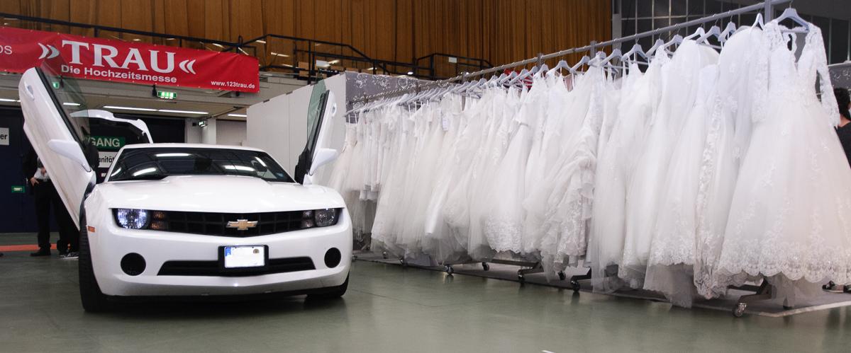 Brautkleider  und Limousine stehen nebeneinander auf der Hochzeitmesse. Bräutigem und Braut werden auf der Messe fündig.