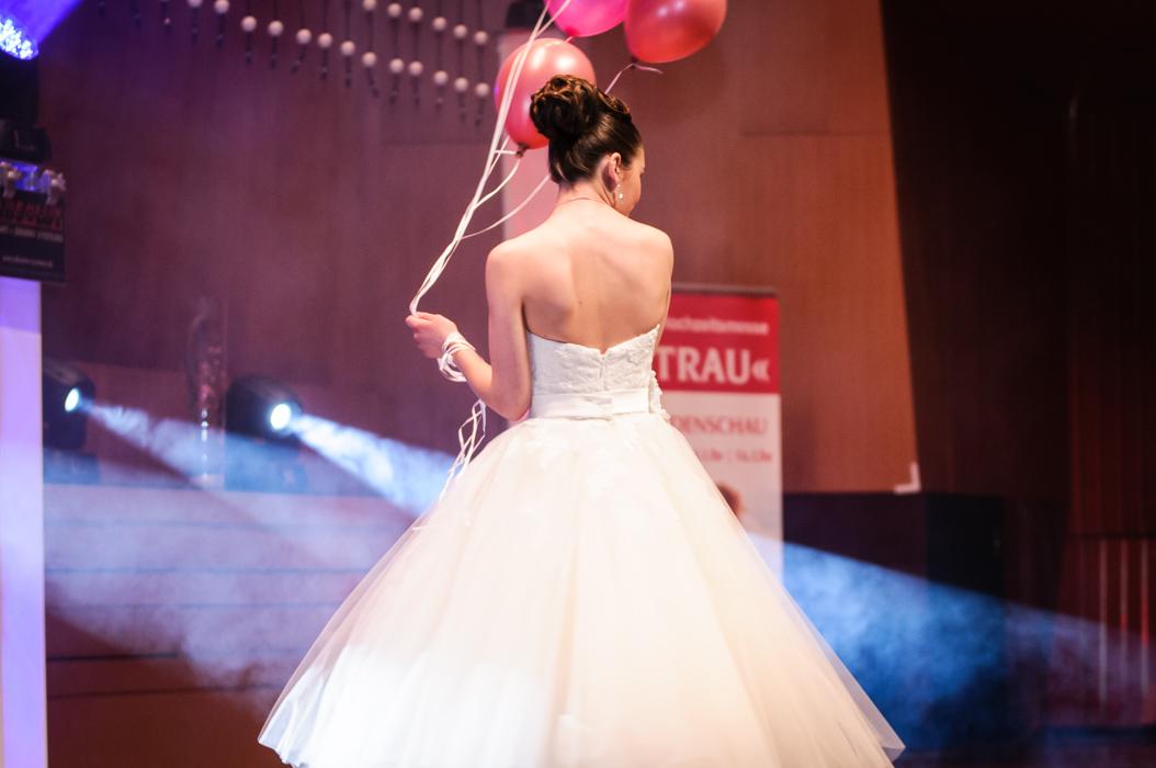 ein Model im  leuchtend weisse Brautkleid mit roten Luftballons. Angestrahlt von Scheinwerfern. Die Braut steht bei der Hochzeitsmesse sicherlich im Mittelpunk. Und darf sich als Prinzessin fühlen.
